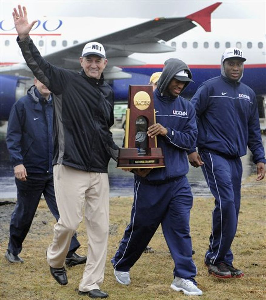 Connecticut head coach Jim Calhoun, left, walks with seniors Kemba Walker, center, and Donnell Beverly, right, as they arrive for a rally at Bradley International Airport in Windsor Locks, Conn., Tuesday, April 5, 2011.  Connecticut beat Butler for the National championship in the NCAA Mens Final Four basketball tournament on Monday, April 4. (AP Photo/Jessica Hill)