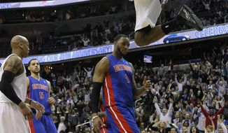 Washington Wizards' John Wall, top, scores a slam dunk while teammate Maurice Evans, left, and Detroit Pistons' Tracy McGrady (1) and Austin Daye (5) look on during the second half of an NBA basketball game in Washington, Tuesday, April 5, 2011. Wizards won 107-105. (AP Photo/Manuel Balce Ceneta)