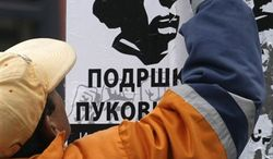 """A man walks pass a poster showing Libyan leader Moammar Gadhafi and reading """"Support for Gadhafi"""", in Belgrade, Serbia, Tuesday, April 5, 2011. Serb support for the Libyan leader grows amid an escalating war in the country that reminds them of their own suffering under NATO bombs.(AP Photo/Darko Vojinovic)"""