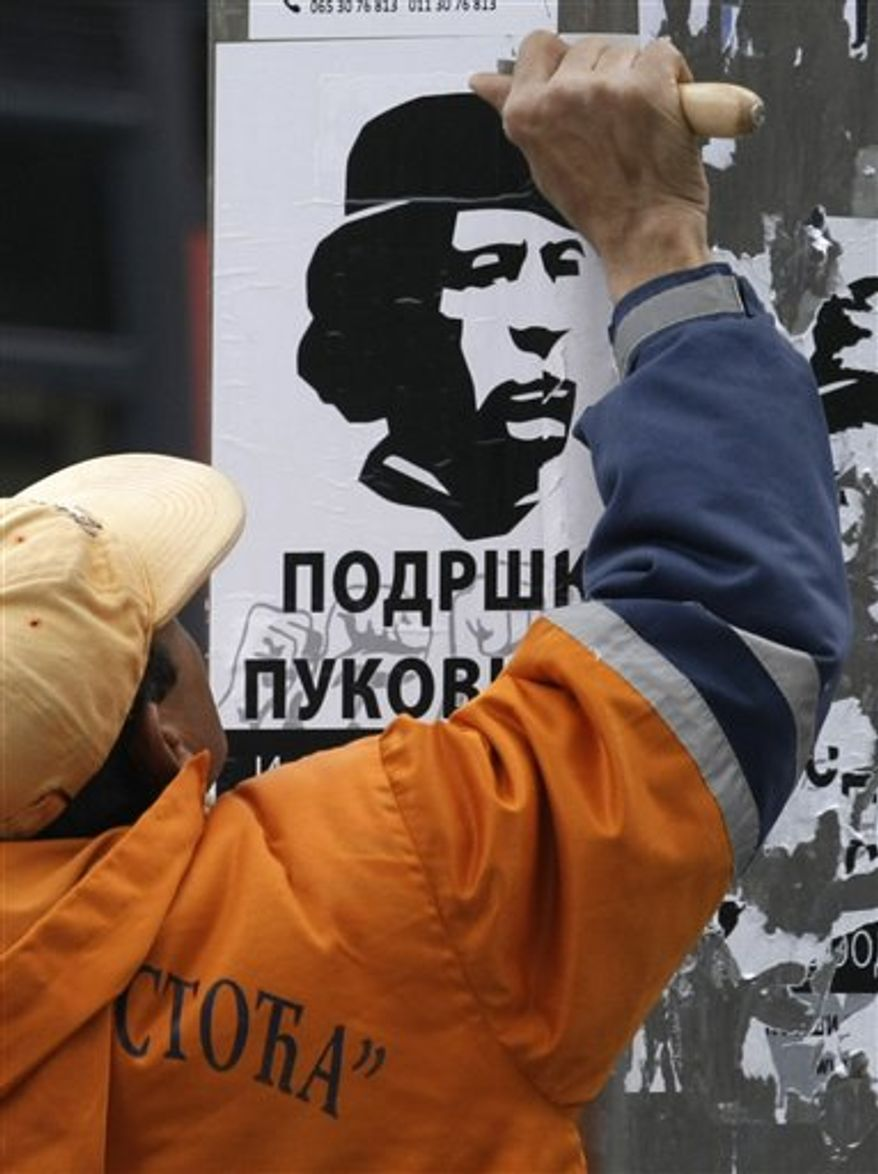 "A man walks pass a poster showing Libyan leader Moammar Gadhafi and reading ""Support for Gadhafi"", in Belgrade, Serbia, Tuesday, April 5, 2011. Serb support for the Libyan leader grows amid an escalating war in the country that reminds them of their own suffering under NATO bombs.(AP Photo/Darko Vojinovic)"