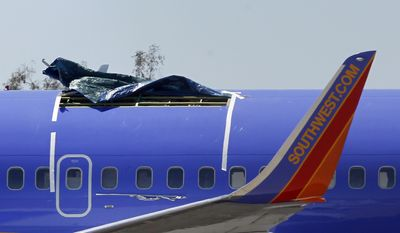 A Southwest Airlines Boeing 737-300 sits in a remote area of the Yuma International Airport in Yuma, Ariz., on Monday, April 4, 2011, after a 5-foot-long tear in the aircraft's fuselage forced an emergency landing at the airport Friday. (AP Photo/Ross D. Franklin)