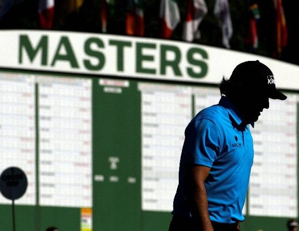 Phil Mickelson (above) walks up to the ninth hole during a practice round for the Masters on Wednesday in Augusta, Ga. Tiger Woods (below) waits to hit off the 13th