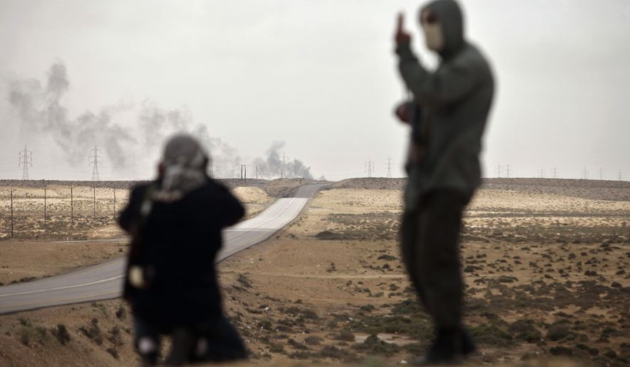 A Libyan rebel (left) looks through his binoculars as his fellow rebel makes a signal as shells explode at a distance on the front line near Brega, Libya, on Wednesday, April 6, 2011. (AP Photo/Altaf Qadri)