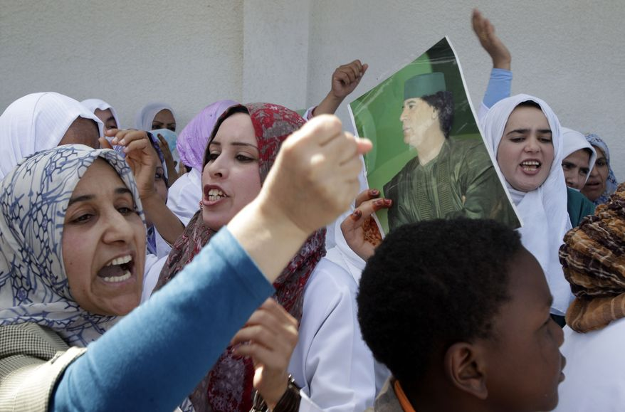 In this image taken during a trip organized by Libyan authorities, hospital staff demonstrate in support of Col. Moammar Gadhafi at the Zawiya Teaching Hospital, where rebels sought treatment during fighting almost three weeks ago, in the coastal city of Zawiya, Libya, 30 miles west of Tripoli, on Tuesday, April 5, 2011. (AP Photo/Pier Paolo Cito)