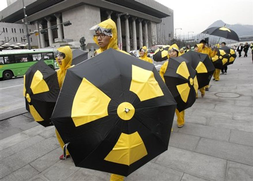 South Korean environmentalists hold umbrellas beside jets of water during a rally demanding South Korean government to stop expanding nuclear power plants in Seoul, South Korea, Wednesday, April 6, 2011. Fears over possible radiation contamination are growing in South Korea, the country closest to Japan, after Japanese nuclear power plants were damaged by earthquakes last month.(AP Photo/Ahn Young-joon)