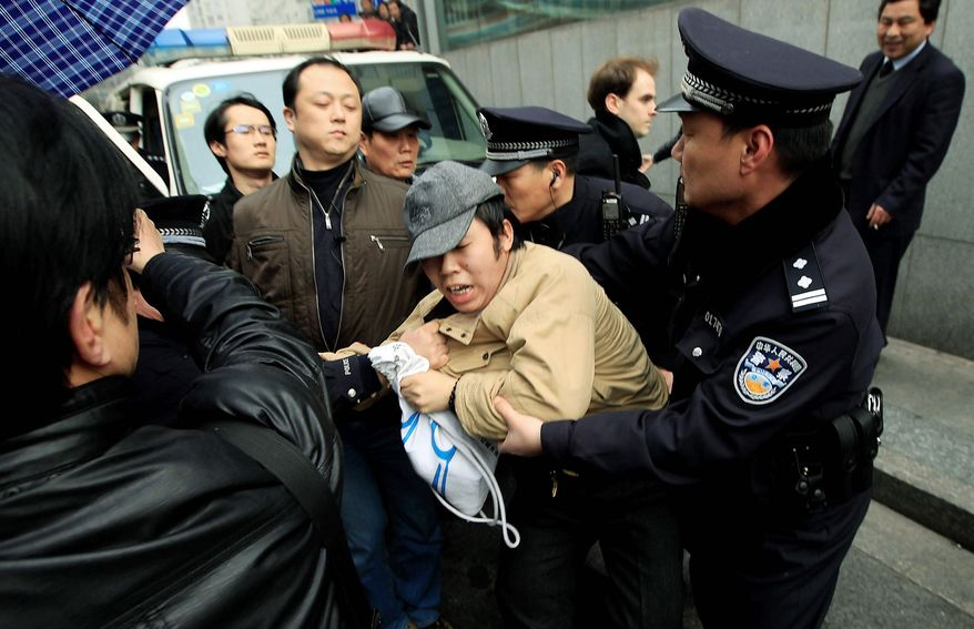 """An unidentified man is detained by police officers near a planned protest site in Shanghai, China. Anonymous calls online for pro-democracy protests in China have prompted the government to launch a sweeping campaign of repression to keep the """"Jasmine Revolution"""" from reaching its shores. (Associated Press)"""