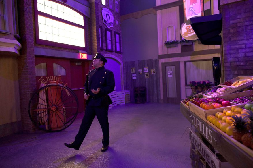 An actor playing a beat cop walks through a set at the exhibit. (Associated Press)