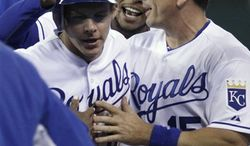 Kansas City Royals' Chris Getz, left, is congratulated by Matt Treanor (15) and Jeremy Jeffress after Getz's scored the game-winning run off of a Melky Cabrera single in the 12th inning of a baseball game, Tuesday, April 5, 2011, in Kansas City, Mo. The Royals beat the Chicago White Sox 7-6. (AP Photo/Ed Zurga)