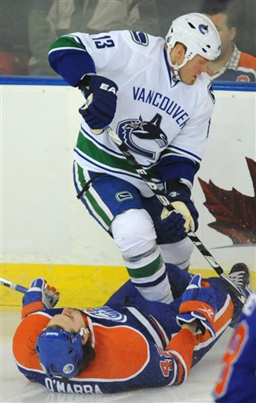 Edmonton Oilers'  Ryan O'Marra, bottom, collides with Vancouver Canucks Raffi Torres during the first period of an NHL hockey game in Edmonton, Alberta, on Tuesday, April 5, 2011. (AP Photo/The Canadian Press, John Ulan)