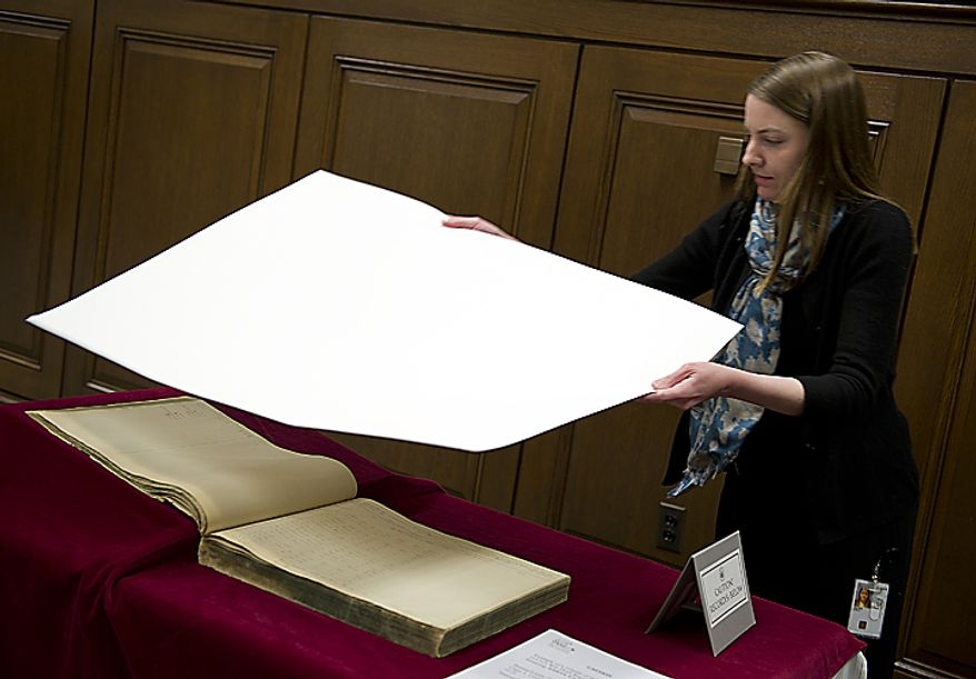Paper conservator Annie Wilker, who works at the National Archives in Washington, unveils a volume that contains a register of Civil War draftees during an announcement on Wednesday, April 6, 2011, at the archives that Civil War documents such as this will now be made available online outside the archives. (Barbara L. Salisbury/The Washington Times)