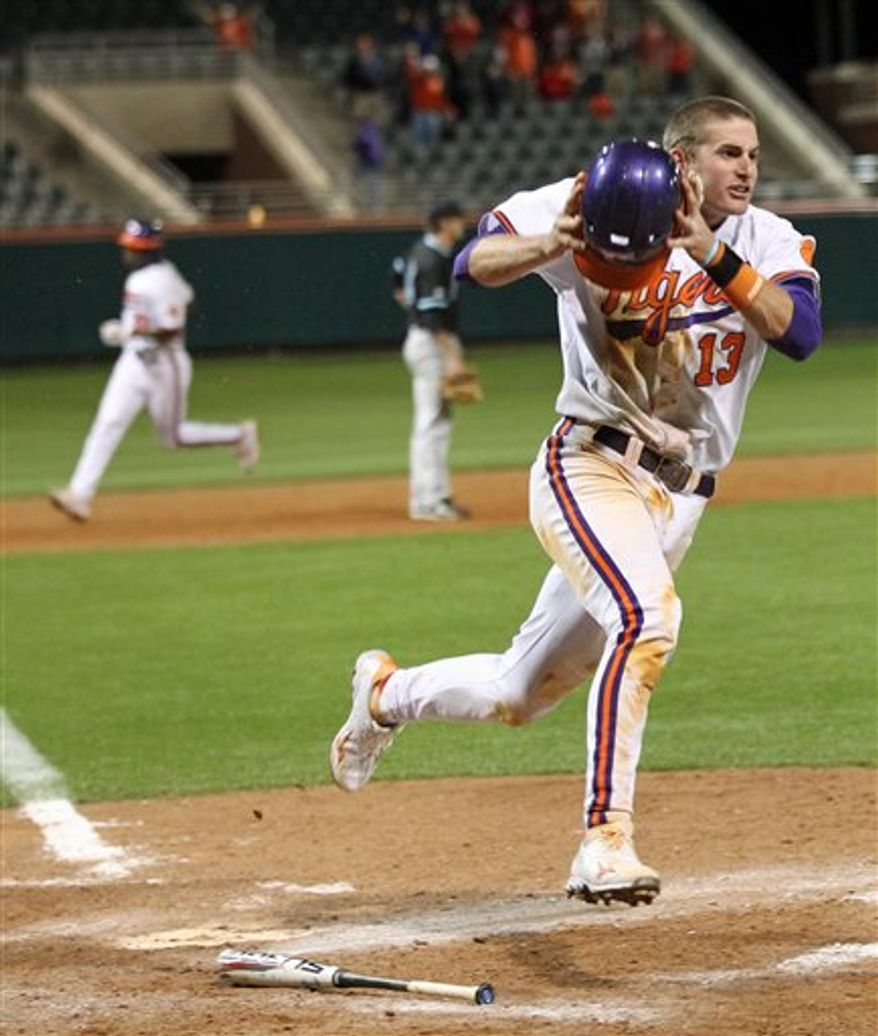 Clemson's Brad Miller crosses home plate with the winning run following Jon McGibbon's bases-loaded single in the 10th inning of a college baseball game against Coastal Carolina at Doug Kingsmore Stadium in Clemson, S.C., on Tuesday, April 5, 2011. Clemson won 5-4. (AP Photo/Anderson Independent-Mail, Mark Crammer)