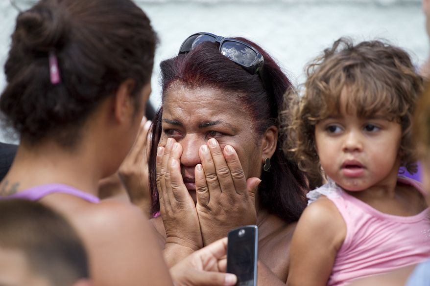 A woman reacts outside a school after a shooting at the school in Rio de Janeiro, Brazil, on Thursday, April 7, 2011. Brazilian authorities say that a gunman opened fire in an elementary school in Rio de Janeiro and at least 13 people are dead, including the gunman. (AP Photo/Victor R. Caivano)