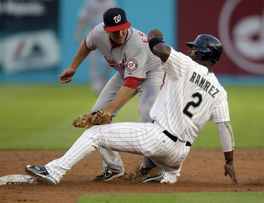 Florida Marlins' Hanley Ramirez (2) is safe at second as Washington Nationals second baseman Danny Espinosa tries to make the play during the first inning of a baseball game in Miami, Wednesday, April 6, 2011. (AP Photo/J Pat Carter)