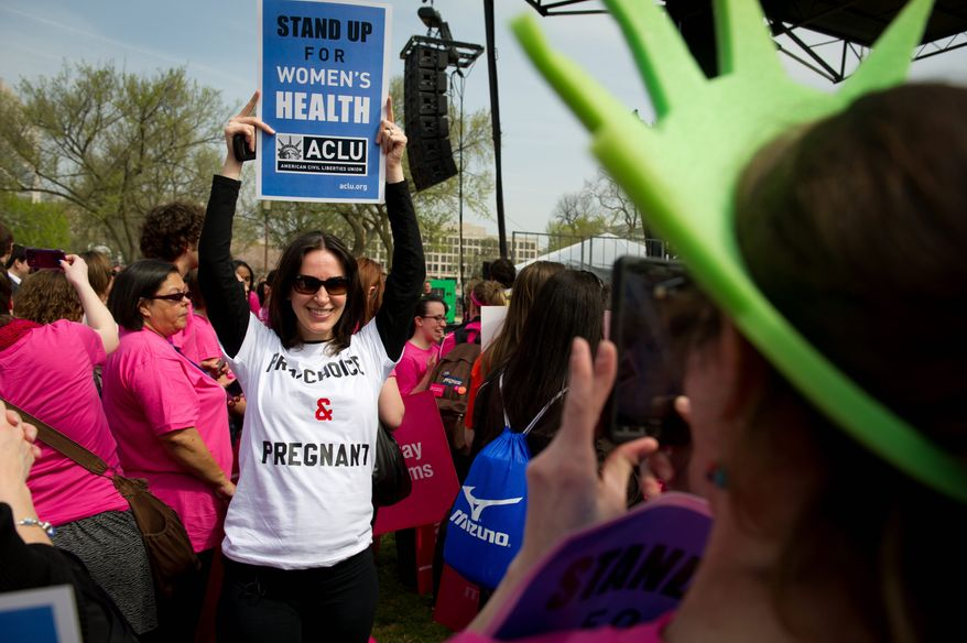 Sondra Goldschein (left) poses Thursday for friend Joanna Diamond (right) as they join in a Stand Up for Women's Health rally on the Mall. The event was sponsored by Planned Parenthood, NARAL Pro-Choice America, and other groups. (Rod Lamkey Jr./The Washington Times)