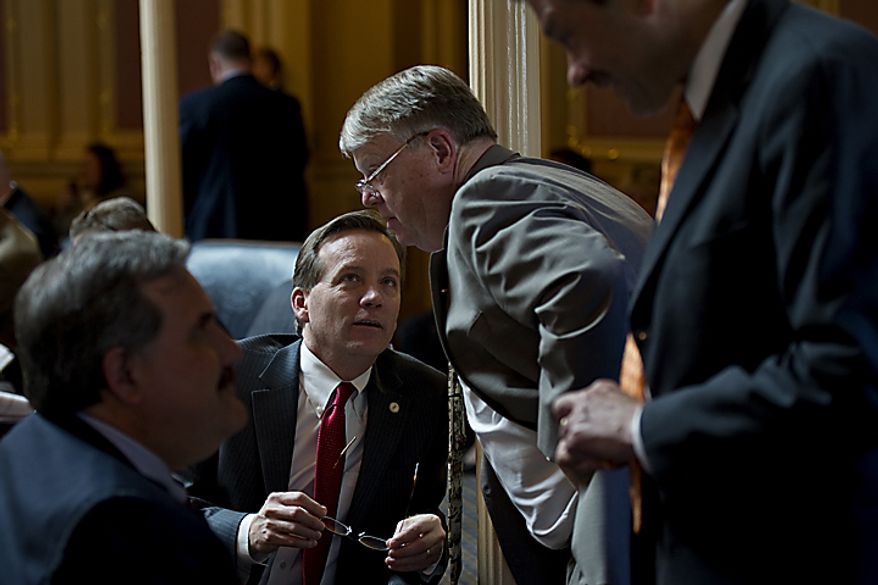 Republican delegates Chris Jones, center, and Scott Lingamfelter, right, talk with each other during debate on governor's amendments on the House floor at the Capitol, in Richmond, Wednesday, April 6, 2011. (Drew Angerer/The Washington Times)