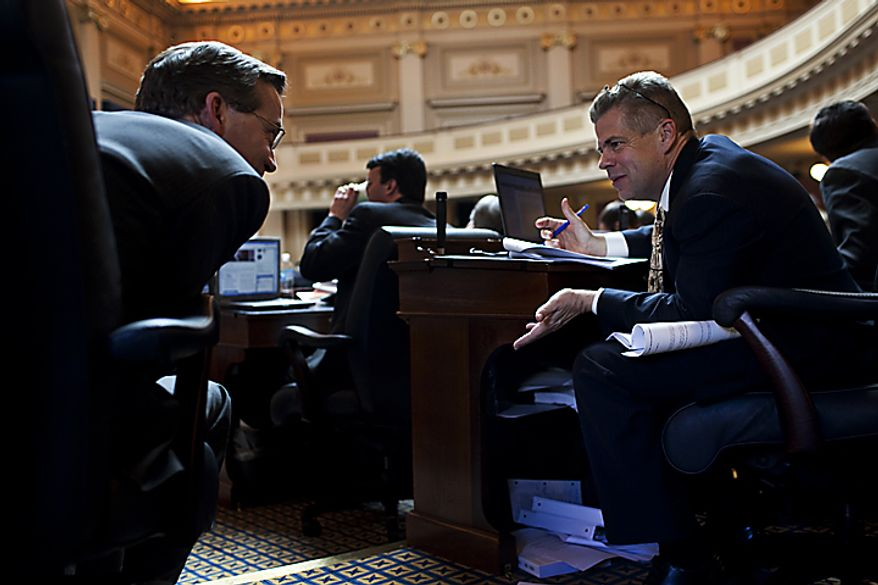 Republican House Majority Leader Kirkland Cox, right, talks with fellow Republican delegate Chris Jones, left, during debate on the Governors budget amendments, on the House floor at the Capitol, in Richmond, Wednesday, April 6, 2011. (Drew Angerer/The Washington Times)