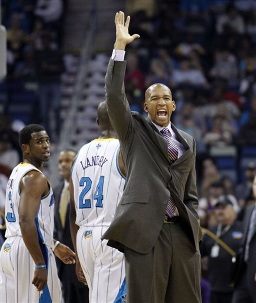 New Orleans Hornets head coach Monty Williams complains to the referees as New Orleans Hornets point guard Chris Paul (3) and power forward Carl Landry (24) walk off court during a timeout in the first half of an NBA basketball game against the Houston Rockets in New Orleans, Wednesday, April 6, 2011. (AP Photo/Gerald Herbert)