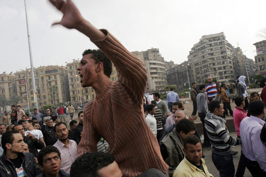 A protester chants slogans while riding on another man's shoulders following an attack by security forces in Tahrir Square, in Cairo, Egypt, Saturday, April 9, 2011. Soldiers beat hundreds of protesters with clubs and fired heavy volleys of gunfire into the air as part of a pre-dawn attack to clear away an overnight demonstration in Cairo's central Tahrir Square, in the latest sign of tensions between Egypt's ruling military and the country's protest movement. (AP Photo/Mohammed Abu Zaid)