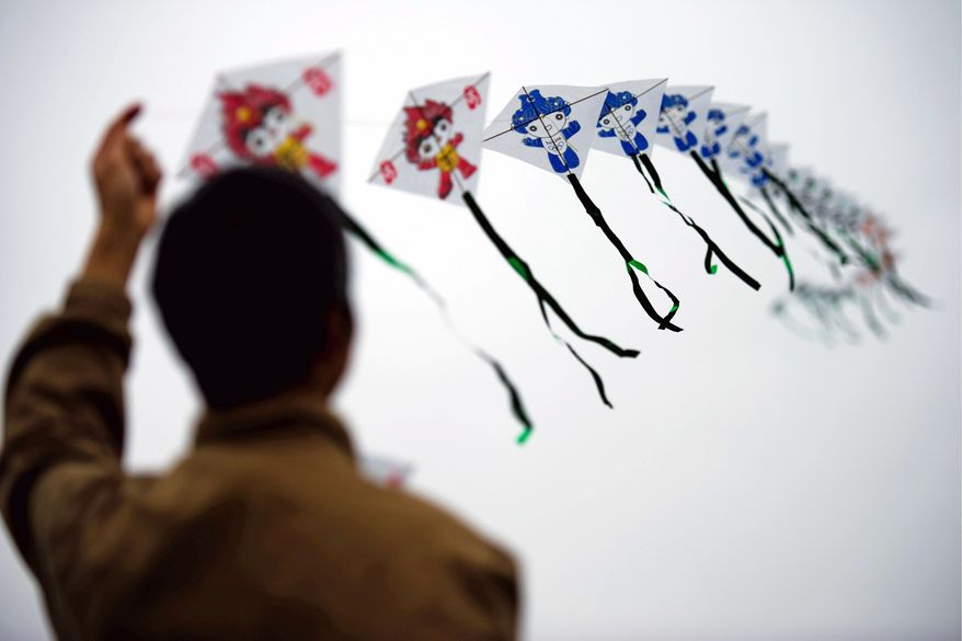 Xian Lin, of Potomac, flies his kite Sunday during the Blossom Kite Festivalon the Mall. His elaborate kite featured the mascots from the Beijing 2008 Olympic Games. To mark the transition from the Smithsonian Kite Festival to the first Blossom Kite Festival, this year's suggested theme was spring and blossom-inspired kites. (Drew Angerer/The Washington Times)