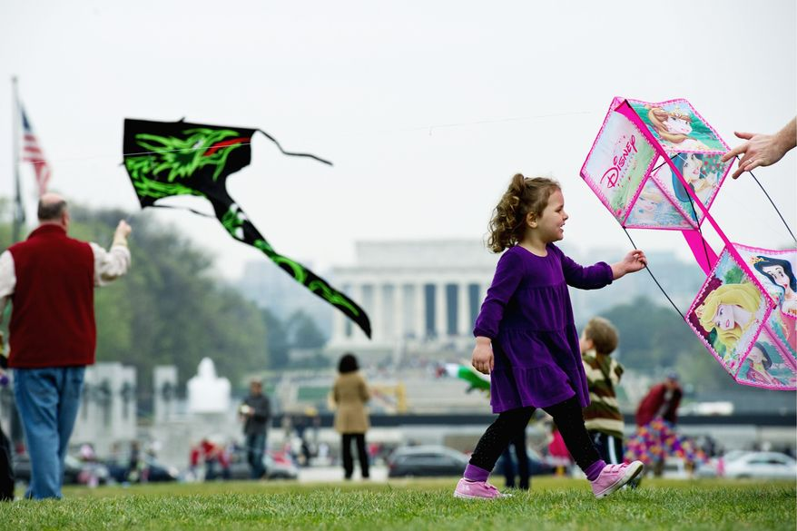 Claire Tarallo, 5, of Herndon, tries to get her Disney kite aloft Sunday at the annual kite festival on the Mall. (Drew Angerer/The Washington Times)