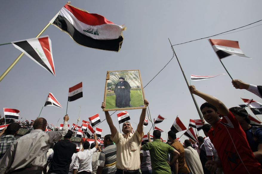 Followers of radical Shiite cleric Muqtada al-Sadr, seen in the poster at center, wave Iraqi flags Saturday during a rally in Baghdad marking the eighth anniversary of the fall of the Iraqi capital to American troops. (Associated Press)