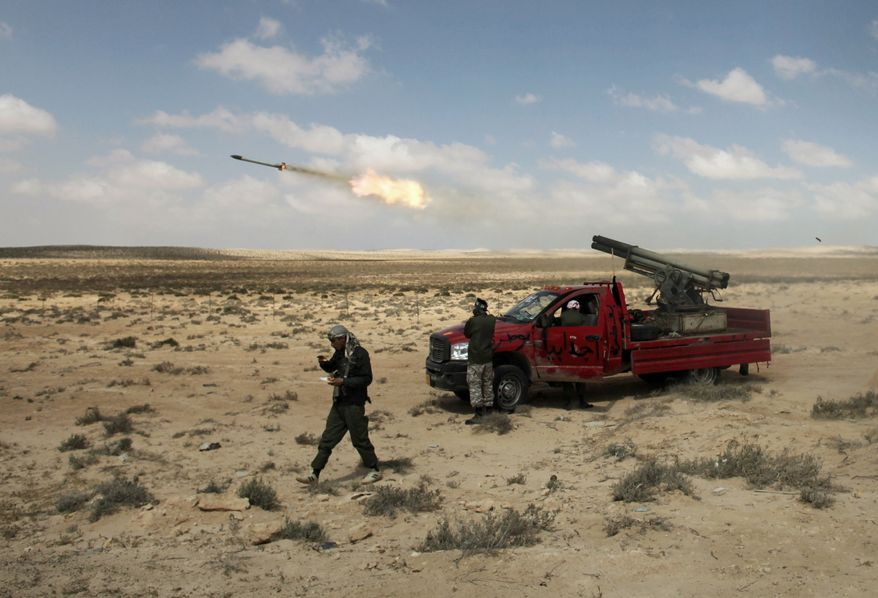 Libyan rebel fighters fire rockets in the desert between Ajdabiya and Brega on Saturday. The rebels said NATO airstrikes Sunday helped them drive Col. Moammar Gadhafi's forces out of Ajdabiya, the gateway to the opposition's stronghold. (Associated Press)