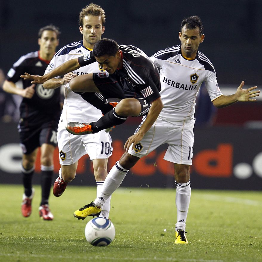 DC United's Andy Najar, center, trips as Los Angeles Galaxy's Mike Magee (18) and Los Angeles Galaxy's Juninho (19) defend during the second half of an MLS soccer game on Saturday, April 9, 2011, in Washington. The game ended in a 1-1 tie. (AP Photo/Luis M. Alvarez)