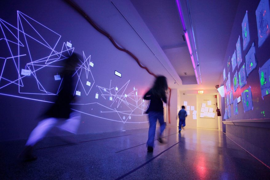Black light illuminates a hallway at the Blue School in New York. The private school was founded by members of the Blue Man Group so they could have a school creative enough for their own children. (Associated Press)