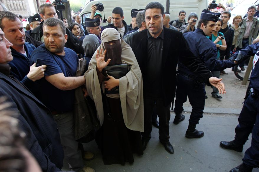 A woman with her face covered by a niqab is taken away by police officers in Paris on Monday, the first day of France's ban on Islamic face veils. The law was met with a burst of defiance, as several veiled women arrived at Notre Dame Cathedral and two were detained for taking part in an unauthorized protest. France is the first country to ban the veils anywhere in public. (Associated Press)