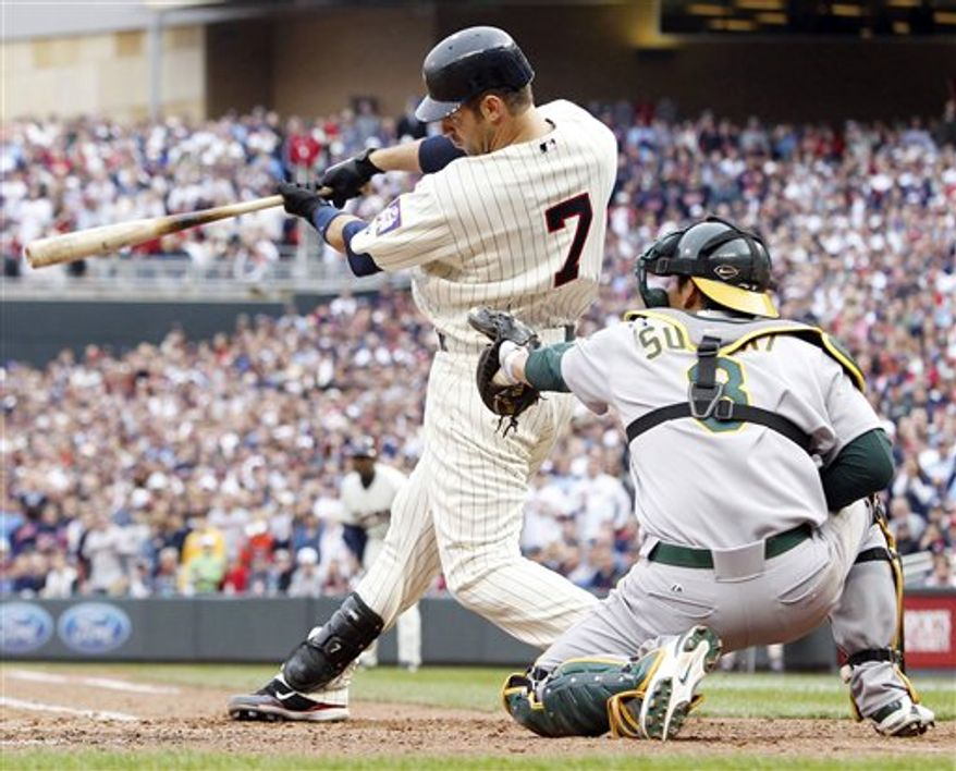 Minnesota Twins' Joe Mauer (7) hits an RBI-single to take the lead 2-1 against Oakland Athletics catcher Kurt Suzuki during the eighth inning of an MLB baseball game on Friday, April 8, 2011, in Minneapolis, Minn. The Twins defeated the Athletics 2-1. (AP Photo/Genevieve Ross)