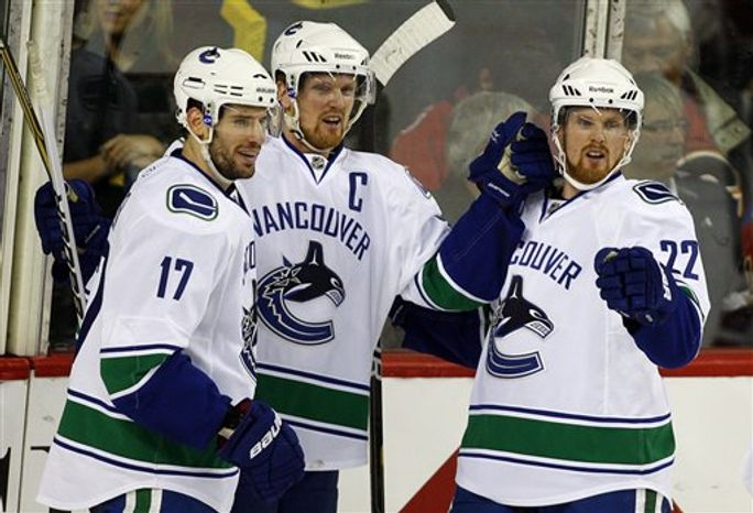 Calgary Flames' Jarome Iginla, center, celebrates his goal with teammates Mark Giordano, left, and Rene Bourque during the second period of an NHL hockey game against the Vancouver Canucks in Calgary, Alberta, Saturday, April 9, 2011. (AP Photo/The Canadian Press, Jeff McIntosh)