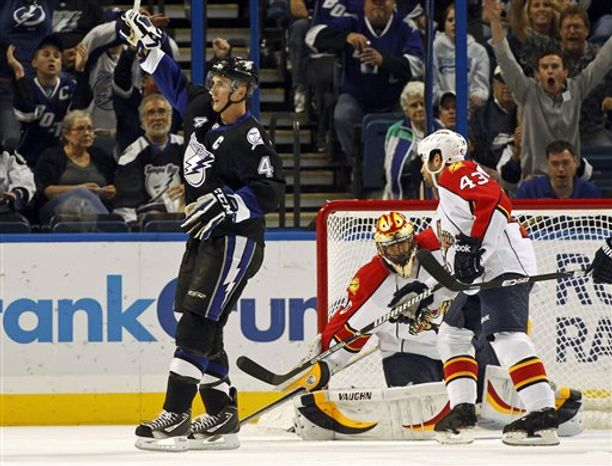 Tampa Bay Lightning's Vincent Lecavalier fights for a rebound in front of Florida Panthers goalie Scott Clemmensen with defenders Marty Reasoner, right, and Mike Weaver during the third period of an NHL hockey game Friday, April 8, 2011, in Tampa, Fla. The Lightning won 4-2. (AP Photo/Mike Carlson)