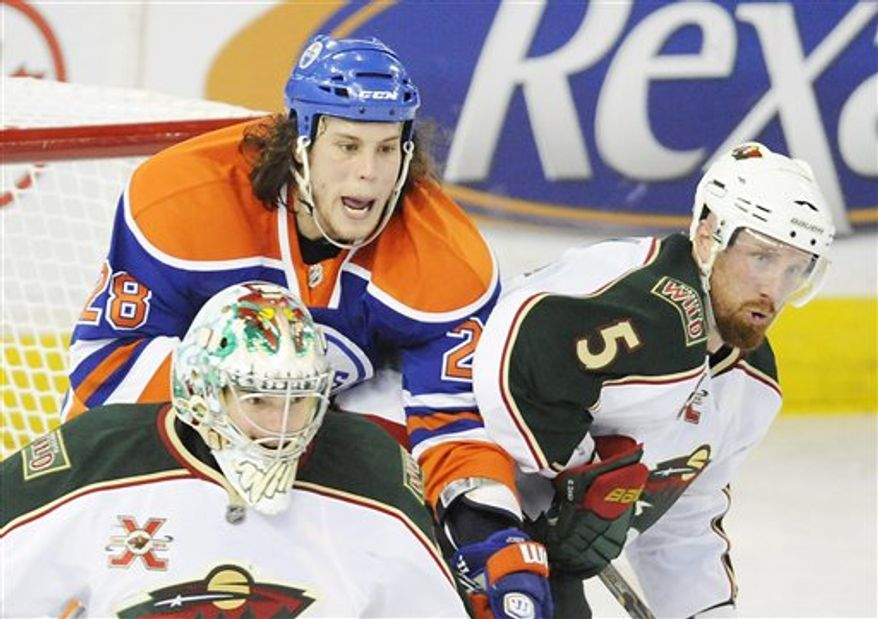 Minnesota Wild goalie Jose Theodore, left, and Greg Zanon, right, battle with the Edmonton Oilers' Ryan Jones during third period NHL hockey action in Edmonton on Friday, April 8, 2011.  (AP Photo/The Canadian Press, John Ulan)
