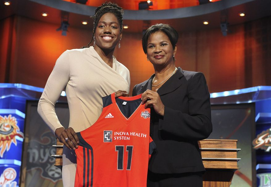 Kentucky's Victoria Dunlap, left, holds up a Washington Mystic's jersey with Renee Brown, WNBA basketball operations head, after the Mystics chose Dunlap with the No. 11 pick in the WNBA basketball draft in Bristol, Conn., Monday, April 11, 2011. (AP Photo/Jessica Hill)