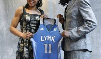 Connecticut's Maya Moore, center, sits with UConn coach Geno Auriemma, left, and her mother, Kathryn Moore, prior to being chosen by the Minnesota Lynx with the No. 1 pick in the WNBA basketball draft in Bristol, Conn., Monday, April 11, 2011. (AP Photo/Jessica Hill)