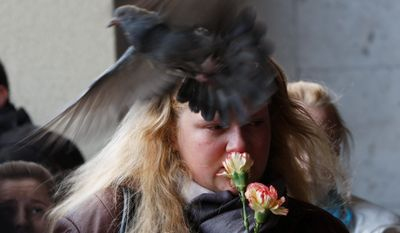A woman mourns as a pigeon passes by her at an entrance to the Oktyabrskaya station of the Minsk subway in Belarus on Tuesday. The Interior Ministry said a bomb placed under a bench on the Oktyabrskaya station exploded on Monday as people were coming off the trains at an evening peak hour. (Associated Press)
