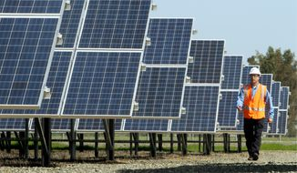 Greg Bosscawen, manager of renewable energy for Pacific Gas and Electric Co., walks past solar panels at PG&E's Vaca-Dixon solar energy site near Vacaville, Calif., on Tuesday. Gov. Jerry Brown signed legislation Tuesday that would require California utilities to get one-third of their power from renewable sources. (Associated Press)
