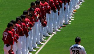 The Rakuten Golden Eagles, a professional team representing disaster-wracked Sendai in northeastern Japan, along with fans in the stands, observe a moment of silence for victims of the March 11 earthquake and tsunami before their baseball game against the Lotte Marines in Chiba, near Tokyo, on Tuesday, when the 2011 pro baseball regular season opened in Japan. (Associated Press)