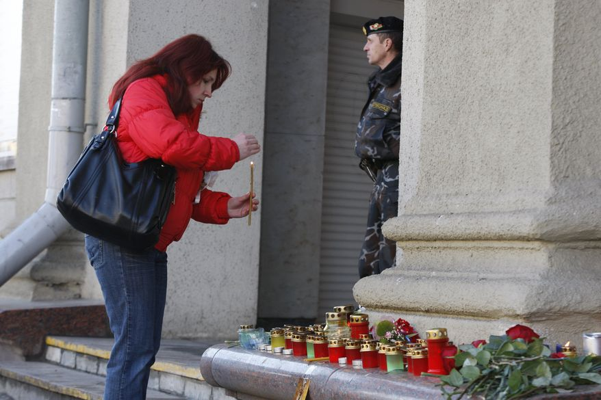 A woman lights a candle at an entrance to the Oktyabrskaya station of Minsk subway in downtown on Tuesday, April 12, 2011. Belarusian authorities said Tuesday they have identified a suspect in a subway bombing as the death toll rose to 12, with more than 200 wounded. (AP Photo/Sergei Grits)