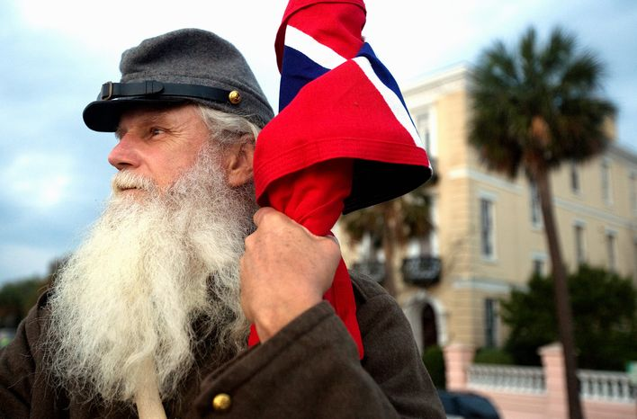 ** File ** At a Civil War reenactment event, a man holds a Confederate naval jack flag as he looks toward Fort Sumter from the Battery in downtown Charleston, S.C., on April 12, 2011, to mark the 150th anniversary of the start of the Civil War. (Associated Press)