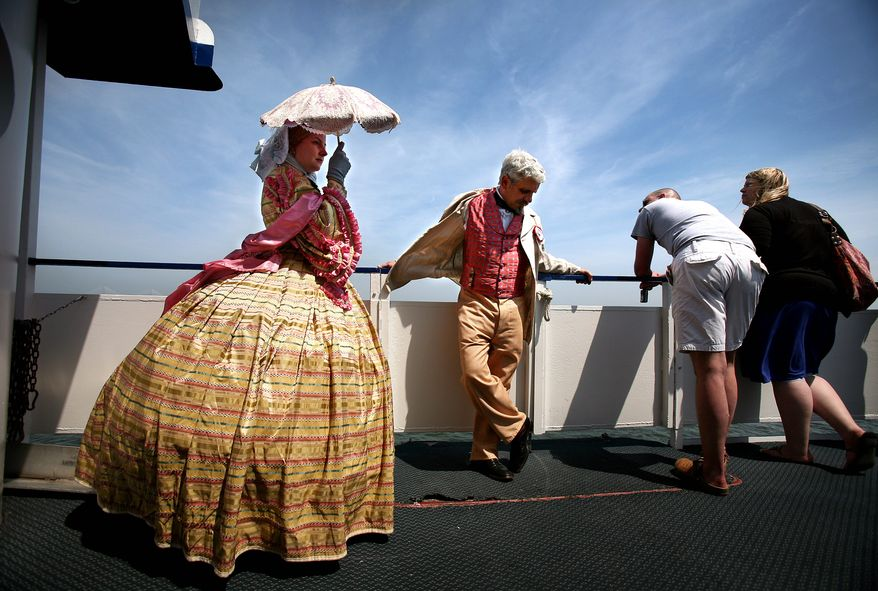 Re-enactors Heather Kenney and her husband, Thomas Mark, of Winchester, Va., enjoy the breeze as they take a tour boat to Fort Sumter on Monday, April 11, 2011, in Charleston, S.C. (AP Photo/The Post and Courier, Grace Beahm)