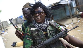 Republican forces soldier Abdoulaye Sanogo (front) wears a wig he said belonged to Simone Gbagbo, wife of Ivory Coast strongman Laurent Gbagbo, on Tuesday, April 12, 2011. The wig was found in her bedroom at the presidential residence as forces allied with President Alassane Ouattara captured the Gbagbos on Monday. (AP Photo/Rebecca Blackwell)