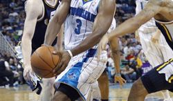 New Orleans Hornets point guard Chris Paul (3) drives to the basket between Utah Jazz small forward Gordon Hayward, left, and point guard Devin Harris in the second half of an NBA basketball game in New Orleans, Monday, April 11, 2011. the Jazz won 90-78. (AP Photo/Gerald Herbert)