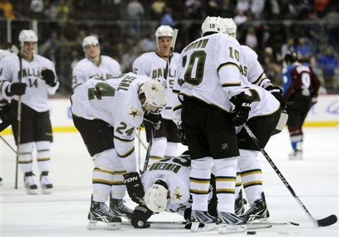 Dallas Stars center Mike Ribeiro, left, defenseman Stephane Robidas, center left, center Steve Ott, center right, and left wing Brenden Morrow, right, celebrate a goal by Ribeiro in the first period of an NHL hockey game against the Colorado Avalanche in Denver on Friday, April 8, 2011. (AP Photo/Chris Schneider)
