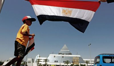 Egyptian Abdallah Hassan, 7, demonstrates Wednesday with his family (holding the national flag) in front of the Sharm-el-Sheikh hospital where ex-President Hosni Mubarak is being detained as criminal charges against him are investigated. (Associated Press)