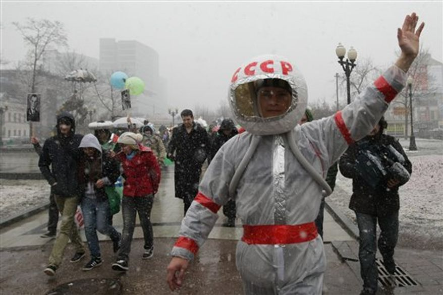 People participate in a flashmob rally to mark the 50th anniversary of Yuri Gagarin's mission, the first human spaceflight, in downtown  Moscow, Tuesday, April 12, 2011. The letters on helmet are acronym for the USSR, Union of the Soviet Socialist Republics. (AP Photo/Sergey Savostyanov)