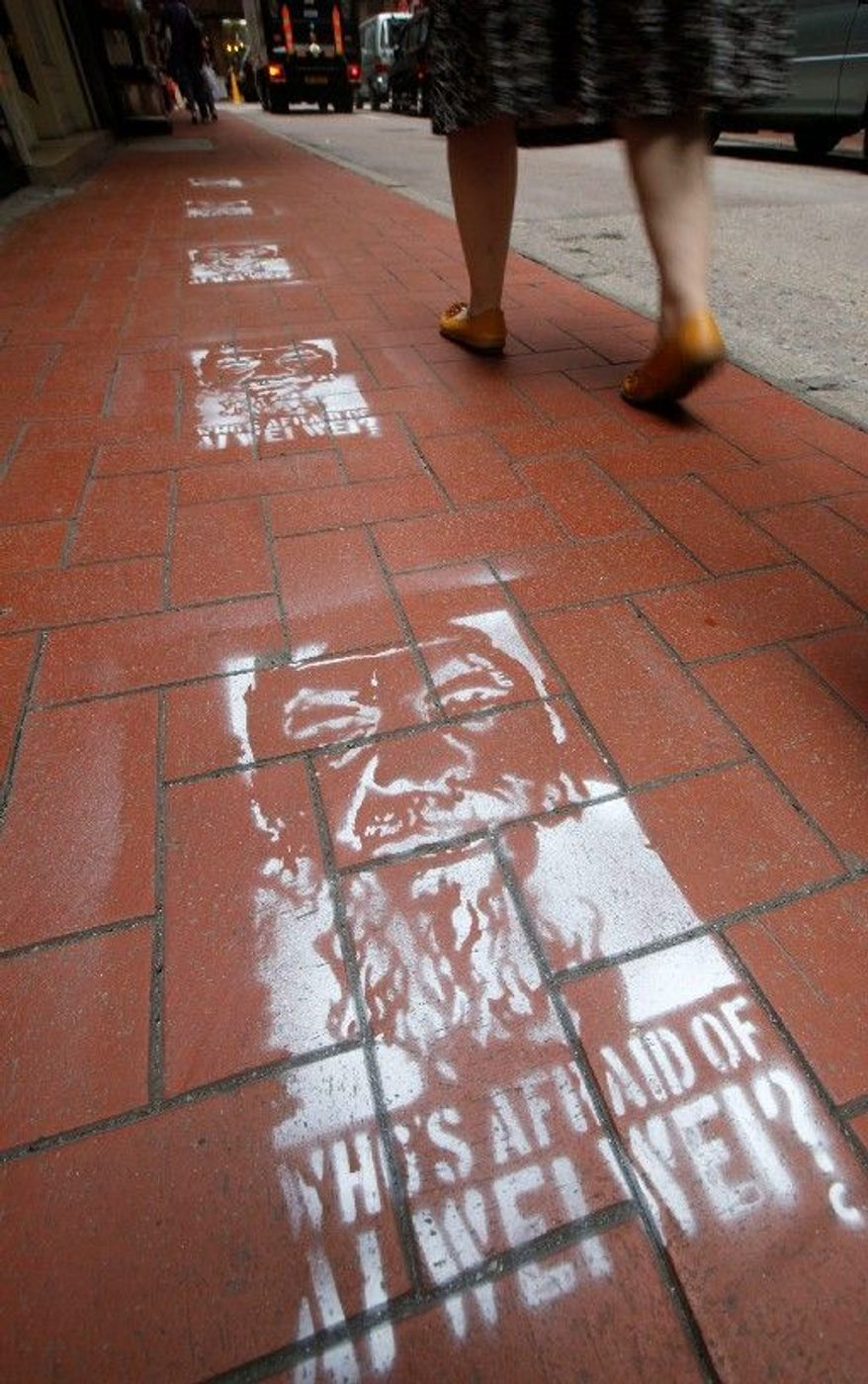 """Detained Chinese artist Ai Weiwei's likeness is sprayed on a Hong Kong sidewalk with the words, """"Who's afraid of Ai Weiwei?"""" The social activist was taken into police custody April 3 and is being investigated for allegedly evading his taxes, a Hong Kong newspaper reported. (Associated Press)"""