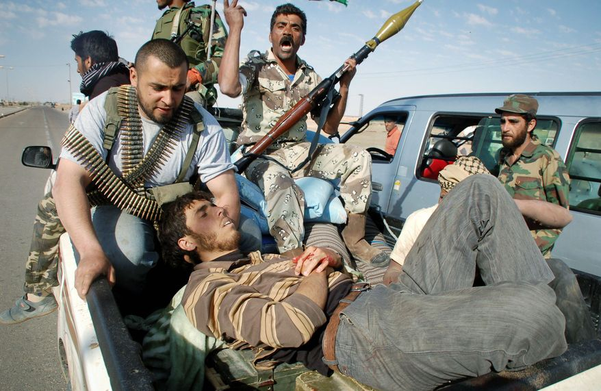 A wounded rebel fighter rides in a pickup truck taking him to an ambulance that will carry him to a hospital on the outskirts of Ajdabiya, Libya. Britain and France want more NATO airstrikes against the Libyan regime. (Associated Press)