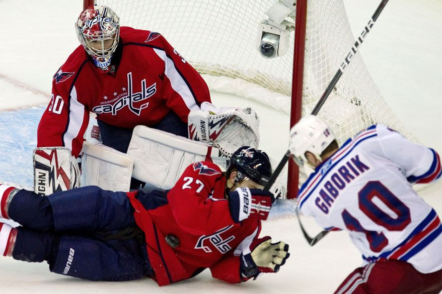 Capitals defenseman Karl Alzner lunges in front of goalie Michal Neuvirth to block a shot by the New York Rangers' Marian Gaborik during Game 1 of their Eastern Conference quarterfinal. Alzner blocked eight shots in Washington's 2-1 win. (Drew Angerer/The Washington Times)