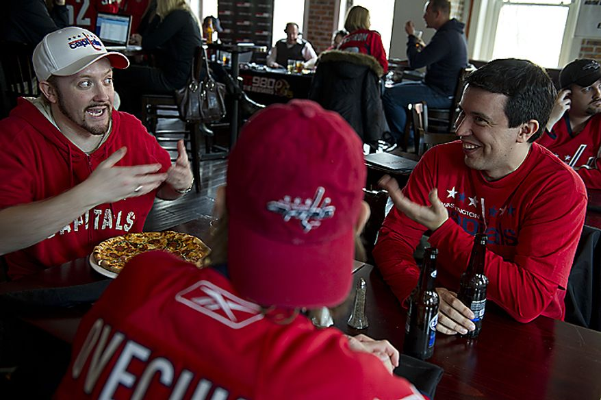 Washington Capitals fans Josh Warrick (left) of Burke, Va., and Will Rodriguez of Arlington, Va., hang out at Redline on G Street Northwest across from the Verizon Center before the first playoff game on Wednesday, April 13, 2011, in Washington. (Barbara L. Salisbury/The Washington Times)
